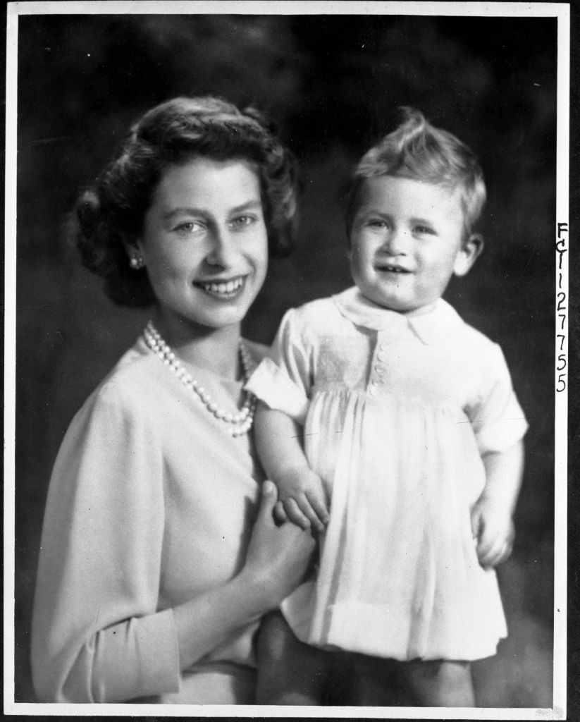 Princess Elizabeth with Princess Charlesshortly before his first birthday in 1949. As was the fashion, Prince Charles is wearing a white infant dress.