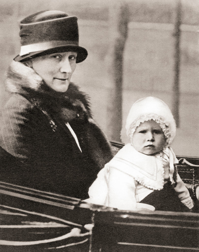 Princess Elizabeth at age two in a bonnet and ruffles. She isriding alongside her nanny, Clara Knight, in 1928.